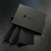 Black A6 Box with Black Sheets of San Francisco Logo and folded black fluidproof plus fabric sample spilling out of box