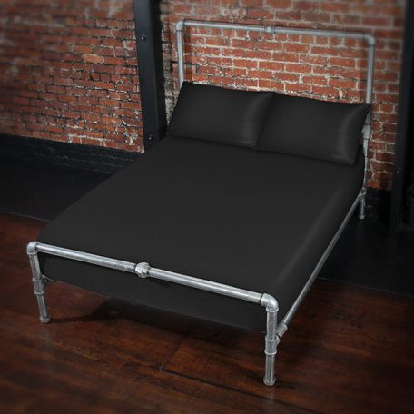 Fluid proof fitted sheet and pillowcases in black on a silver metal bed frame against a brick wall