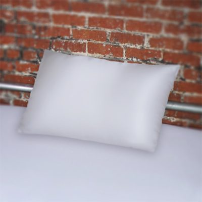 Fluid proof White pillowcase on bed with silver frame against brick wall