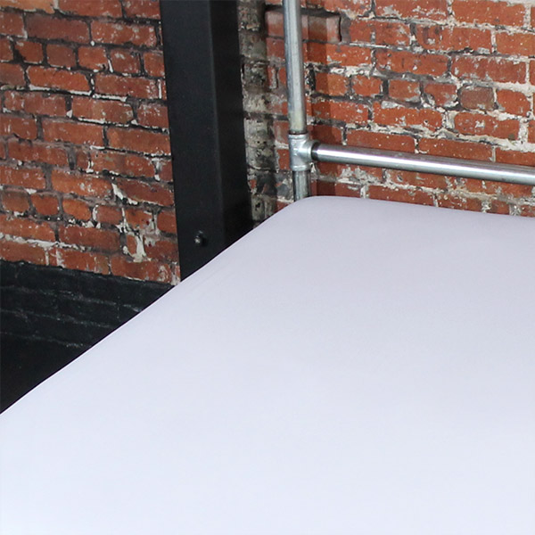 White fluid-proof throw on bed with silver frame against brick wall