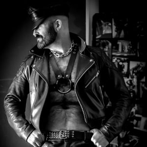 Photo of Joe King in black & white wearing an open leather biker jacket and leather harness