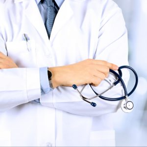 Torso of doctor in white coat holding stethoscope illustrating a post on medical fetishism