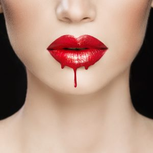close up of white womans face from nose to neck with dripping gloss red lips to suggest a vampire