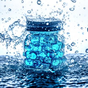 Blue gel beads in a jar in a splash of water