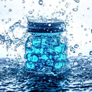 Blue gel beads in a jar in a splash of water